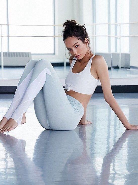 White sports top, light grey/white leggings and deep brown eyes.