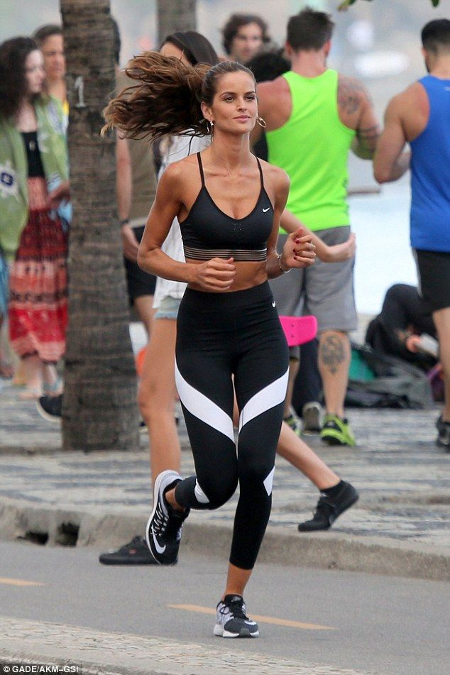 Working it: Her abs flexed as she ran along the coastline with a smile on her fa...