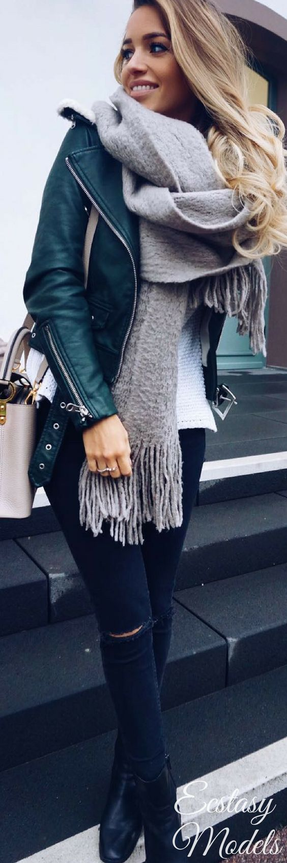 Ella lleva una chaqueta verde y una bufanda gris y patalones negros. La chaqueta...