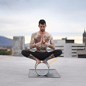garland pose on a yoga wheel. Stretch the hips with hands at heart center